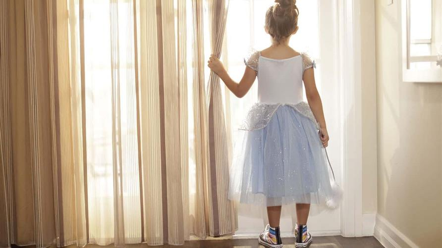 A little girl looking out the window in her Cinderella costume at a Hilton Grand Vacations Orlando resort.