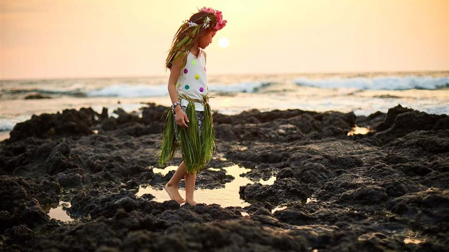 Little girl in grass skirt and lei exploring the rocks along the Pacific shoreline in Hawaii.