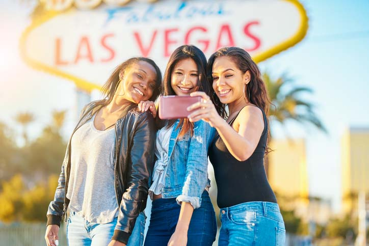 Three girlfriends posing in front the Las Vegas sign on a Hilton Grand Vacations girls' weekend in Las Vegas, Nevada.