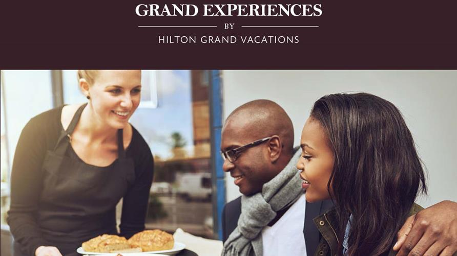 Waitress serving a couple dining out with the Hilton Grand Vacations Grand Experiences card.