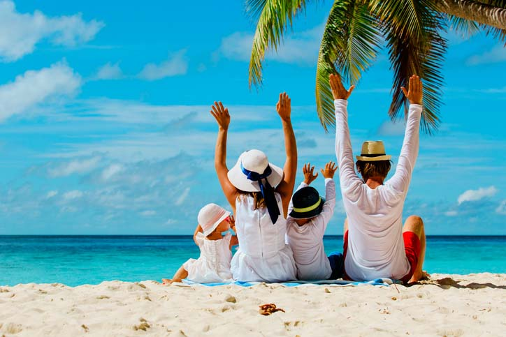 A family sitting under a palm tree looking out at the ocean with arms raised in excitement.