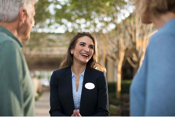 Smiling Hilton Grand Vacations Team Member talking with Owners.