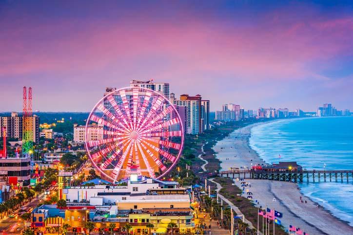 Aerial shot of Myrtle Beach Boardwalk & Promenade and Sky Wheel lighting up with night sky in South Carolina.