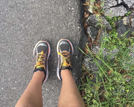 A first person perspective shot of a runner wearing sneakers on a running trail.