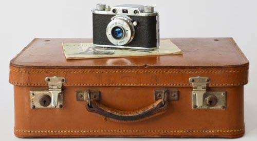 Picture of a classic suitcase with an vintage camera on top.