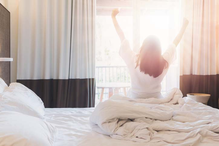 Woman stretching in bed in a Hilton Hotel room looking at the sunrise outside the window.