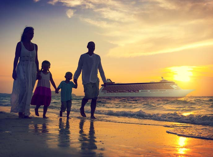 Silhouette of family holding hands and walking on the shoreline at sunset.