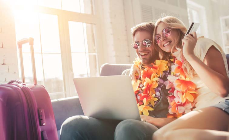 A happy couple wearing leis on their couch booking travel.