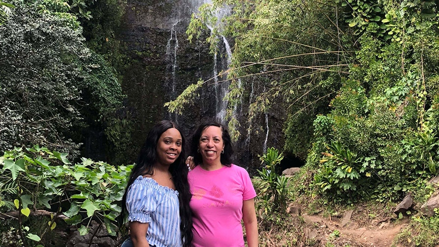 Hilton Grand Vacations Owner and her daughter posing in front of a waterfall on vacation in Hawaii.