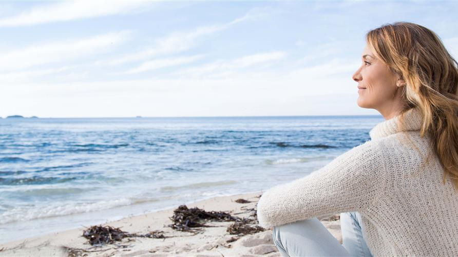 Woman gazing out to the ocean while sitting on the beach.