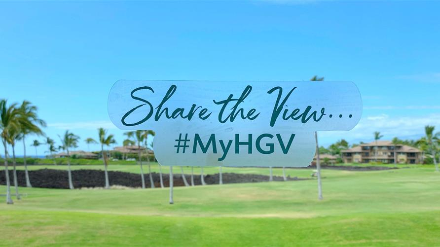 #Sharetheview logo with a Hilton Grand Vacations Hawaii resort golf course in the background.