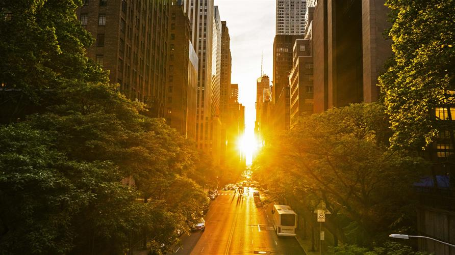 Sunrise over a New York City street between the buildings.