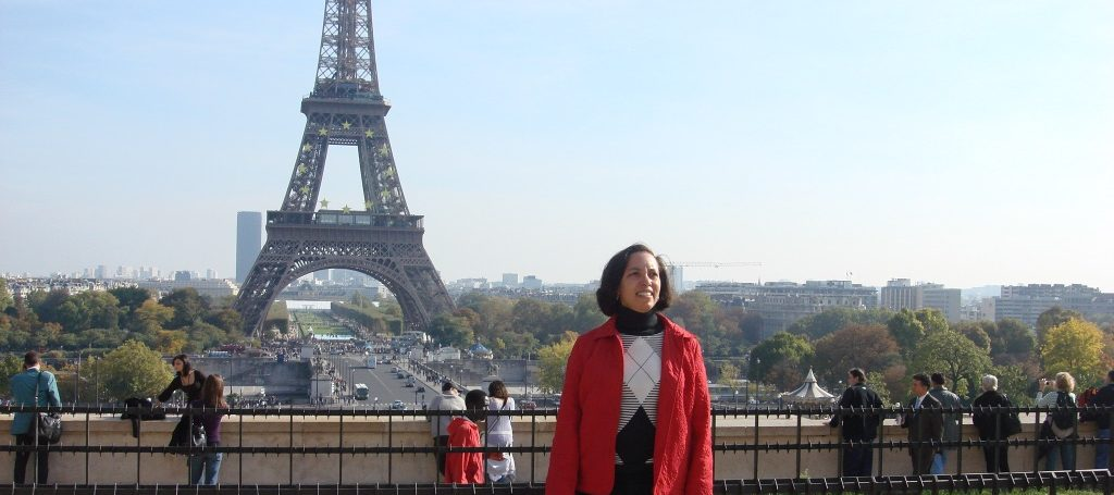 Hilton Grand Vacations Owner smiling and posing in front of the Eiffel Tower in Paris, France.
