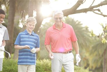 Grandfather and grandson golfing.