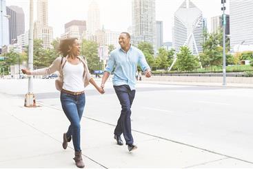 Couple waling through a city park.