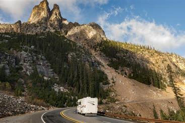RV driving alongside a mountain.