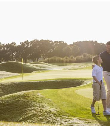 Father and son stroll across a golf course.