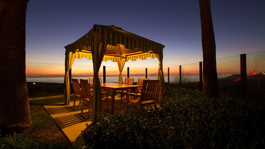 Private cabana with a dining area  overlooking the Pacific Ocean at sunset.