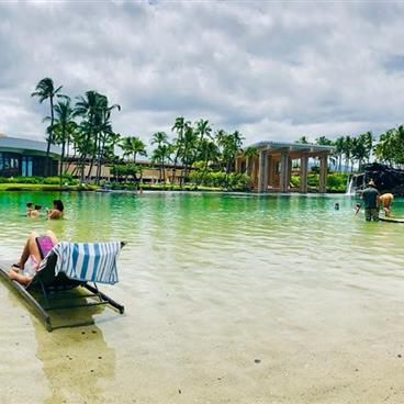 People lounging and playing in a lagoon in Hawaii.