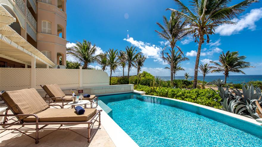 Lounge chairs by clear blue pool at Hilton Grand Vacations at The Crane located in St. Phillip, Barbados.