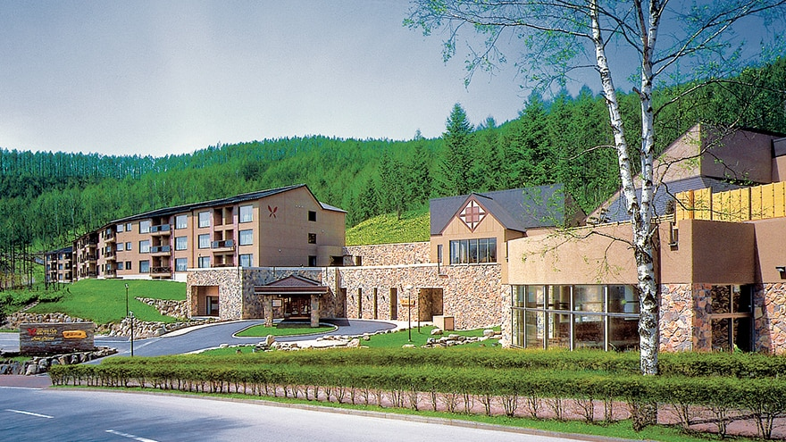 Exterior of Hotel Harvest Tateshina with the mountains in the background.