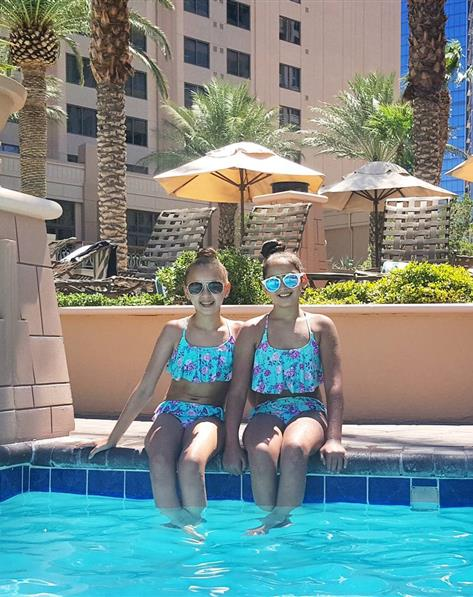 Girls in matching swim suits sit on the edge of a pool on a sunny day.