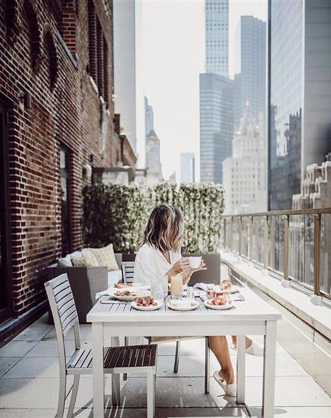 Woman eating lunch on a balcony in New York City.