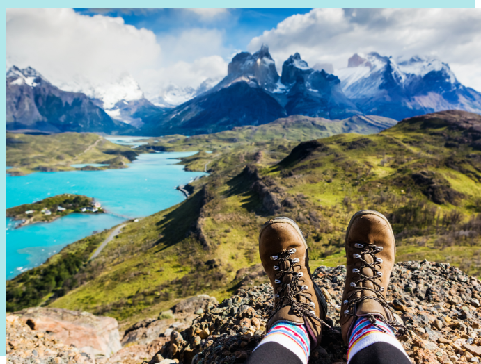 Scenic overlook of rolling, green hills, mountains and lakes, with hike boots in the foreground.